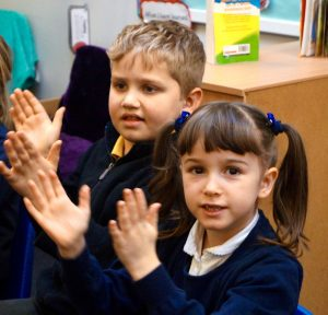 Primary School children singing and clapping